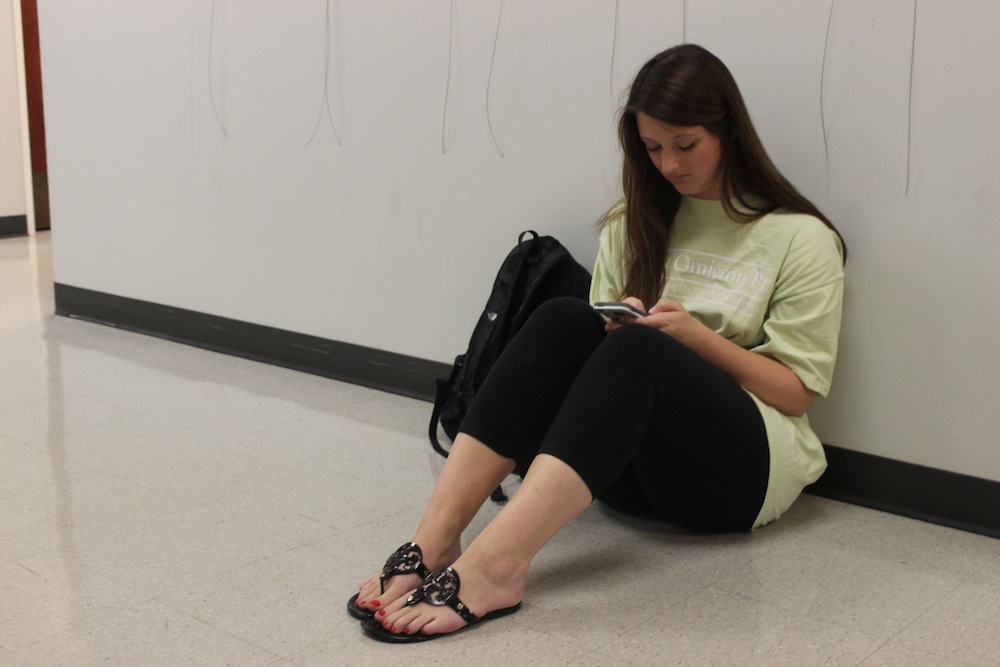 Emily Marshall is a senior studying Integrated Marketing Communications. Marshall is on her phone waiting outside for the other class to end.