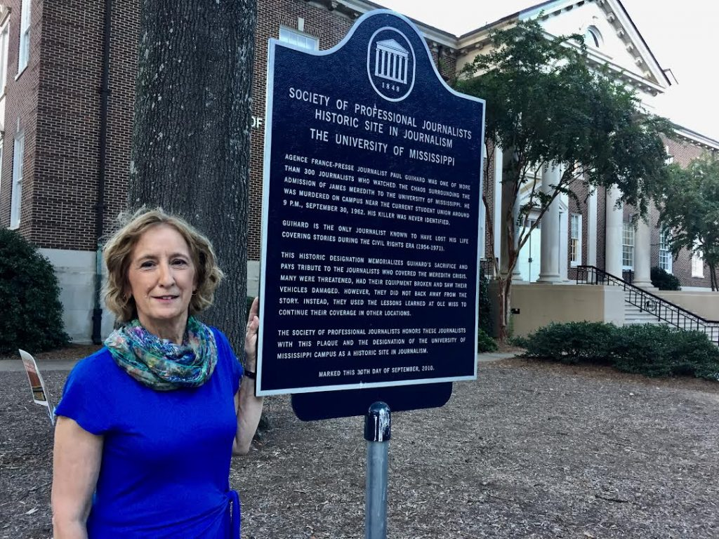 Journalism Professor Kathleen Wickham in front of the plaque honoring Paul Guihard and the 300+ reporters who covered the 1962 integration crisis.