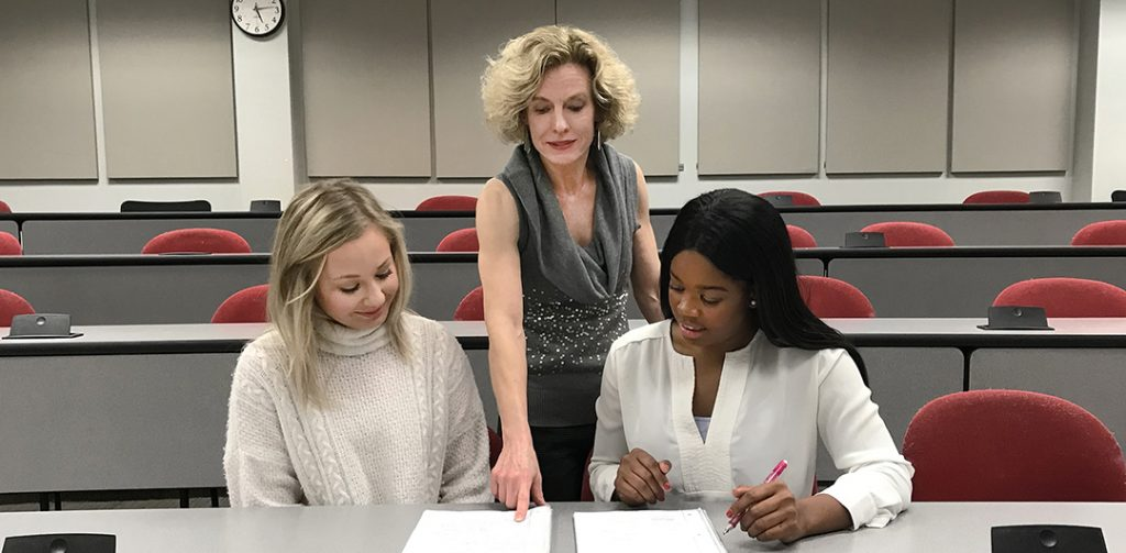Senior Lecturer Robin Street discusses a class project with two students in her PR Case Studies class. From left, are IMC major Jessica Lanter, Street and IMC major Naiomei Young. Photo by Maddie Bridges.