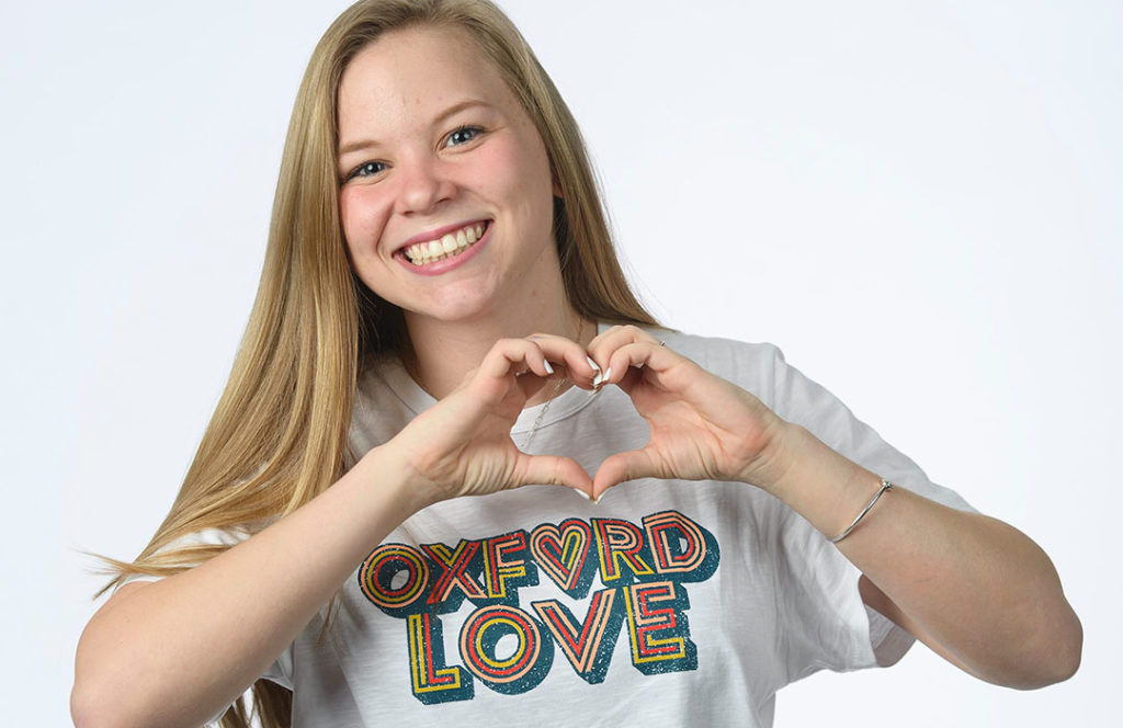 Maggie Walker makes a heart sign while wearing a T-shirt that says Oxford Love
