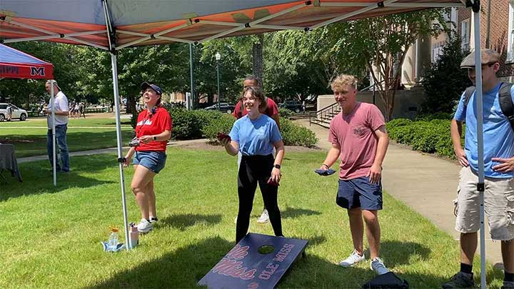Other students and faculty play cornhole at the event.